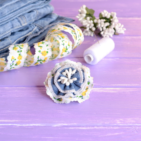 needle laces: Cute flower brooch made from recycled old jeans, lace and artificial stamens. Summer denim brooch, jeans, thread, needles, pins, lace on lilac wooden background. Creative hobby