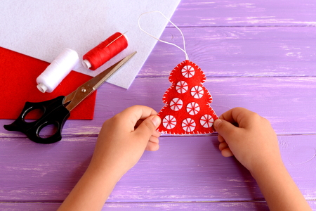 fur tree: Child holds a red felt Christmas tree ornament in his hands. Handicraft red felt fur tree decorated with white balls. Christmas crafts idea for kids. Felt sheets, scissors, thread on wooden background