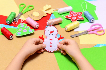 Small child holds a felt Christmas snowman in hands. Child shows Christmas ornament crafts. Beautiful felt Christmas tree ornaments, scissors, thread, needles, felt sheets on a table. Kids festive diy