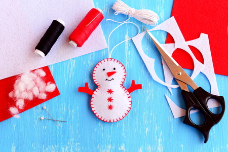 Fun felt Christmas snowman ornament, scissors, thread, needle, pins, cord, felt pieces and scraps on wooden background. How to make a Christmas snowman ornament. Step. Handmade felt crafts. Top view