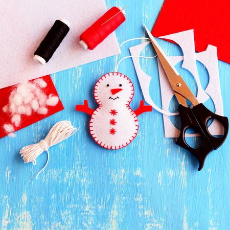 coser: Lindo sentir el ornamento del muñeco de nieve de Navidad, tijeras, hilo, aguja, cuerda, sintieron las hojas y fragmentos en el fondo de madera. Suministros para hacer el muñeco de nieve hecho a mano. navidad niños artesanía idea. Vista superior Foto de archivo