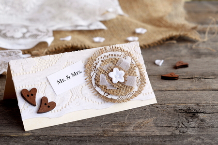 Shabby chic wedding invitation on old wooden table. Vintage wedding card you can create yourself. Idea for wedding invitation decor. Closeup