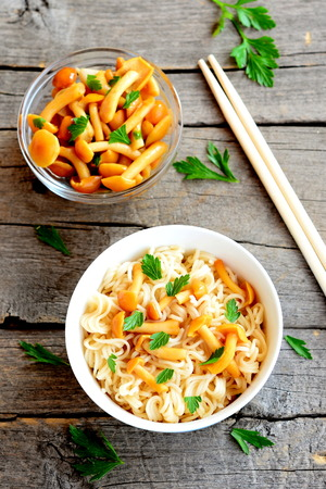 stirred: Pasta with mushrooms and fresh parsley. Vegetarian pasta in a bowl, marinated mushrooms in glass bowl, chopsticks on wooden background. Closeup