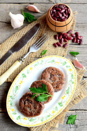 Roasted bean cutlets with garlic and spices on plate. Small decorative barrel with uncooked red beans, garlic, parsley, fork, knife on old wooden background. Healthy vegetarian cutlets. Vintage style Stock Photo