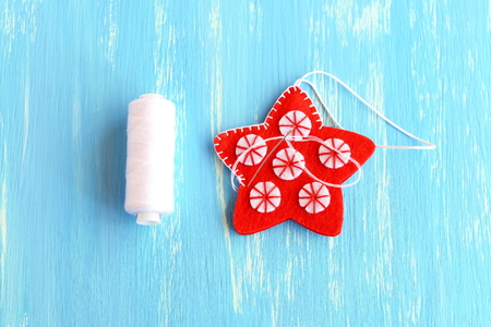 learning by doing: Join the felt edges of Christmas star with white thread using a decorative blanket stitch. Two felt details of Christmas star on a wooden background. Winter diy instruction for kids. Step. Closeup Stock Photo