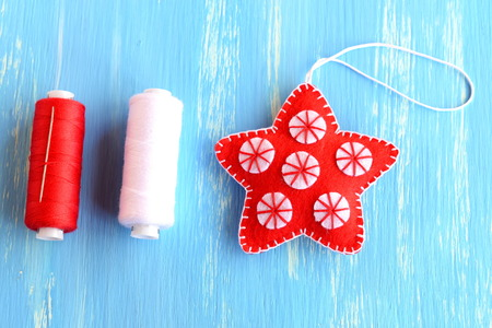 learning by doing: Red Christmas star diy isolated on a wooden background. Handmade felt star with white circles, red and white thread, needle on wooden background. Christmas ornament. Winter kids diy. Closeup. Top view Stock Photo