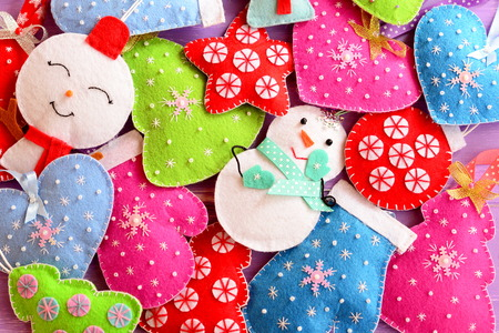 Kids Christmas background. Cute felt ornaments for Christmas. Felt Christmas trees, snowmen, hearts, stars, mittens toys. Top view