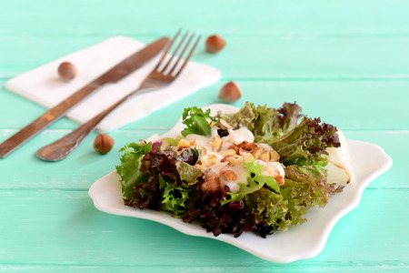 friso: Fresh salad leaves with yogurt and nuts on a plate. Salad is prepared from radicchio, lettuce, iceberg, frieze. Diet food recipe. Fork, knife on a wooden background. Closeup