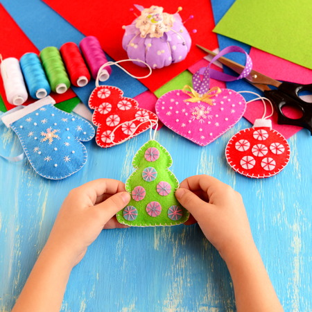 Small child holds felt Christmas tree decor in his hands. Child shows Christmas diy. Felt fur-tree, mitten, heart, ball decor on wooden background. Sewing supplies
