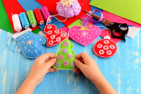 Small child holds felt Christmas tree in his hands. Child shows Christmas crafts. Felt fur-tree, mitten, heart, ball decor on wood background. Flat felt sheets, scissors, sewing set, pins, pincushion