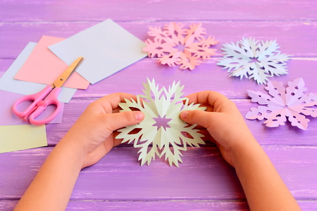 Child holds a paper snowflake in hands. Child shows snowflake decoration. Colored paper, scissors, snowflakes crafts on wooden background. How to make simple structures from a paper. Kids winter art Stok Fotoğraf