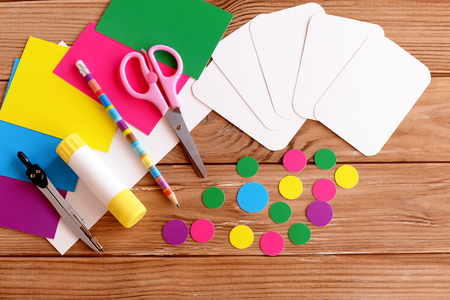 Cut cards and circle, scissors, pencil, glue, colored cardboard sheets on a wooden table. How to make educational flashcards for teaching children color and account. Do it yourself. Step
