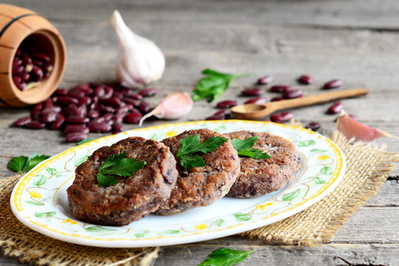 Cutlets made from boiled and mashed red beans on a plate. Scattered uncooked red beans, garlic, fresh parsley, small wooden spoon and decorative barrel on old wooden background. Vintage style. Closeup Stock Photo