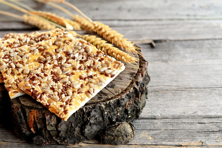 galletas integrales: Galletas sanas con semillas de girasol, semillas de lino y semillas de sésamo y espiguillas de trigo en el fondo de madera vieja. Snack de galletas veganas