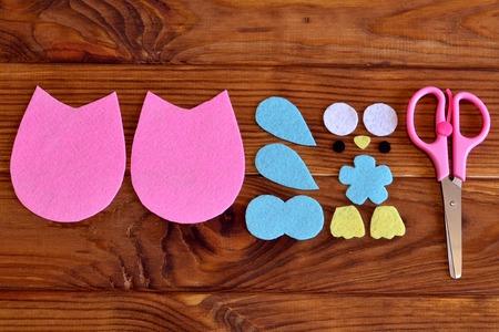 needlecraft: Felt owl patterns, scissors on a wooden table. How to make a cute felt owl embellishment. Kids needlecraft tutorial. Top view. Closeup