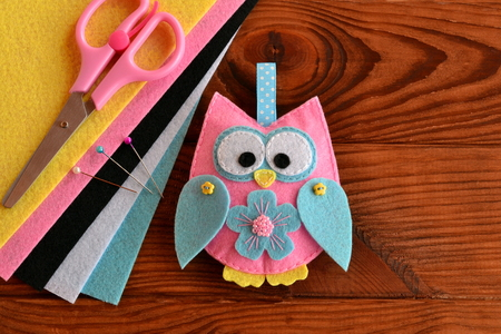 Cute pink and blue owl toy, colored felt sheets, scissors on a wooden table. Fabric owl embellishment. Hand pretty felt ornament. Children crafts project