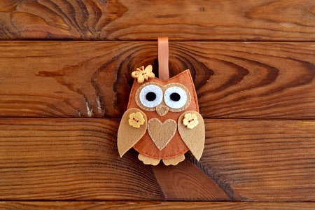 Brown felt owl decorated with heart and buttons in the shape of flowers and butterfly. Home decor for Valentines day, birthday. Cute soft toy isolated on wooden background