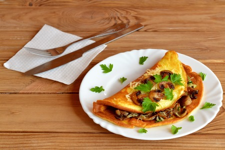 Fried omelette with mushrooms, cheese and green parsley. Stuffed omelette on a plate and on a wooden table. Fork, knife, napkin. Breakfast eggs recipe. Breakfast idea