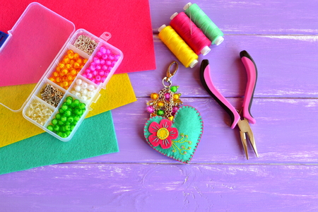 Homemade keychain felt embellished with beads. Colorful fabric heart pendant, woman's or children's accessory. Plastic box, pliers, wool sheets, needle, thread. Set for kids handicraft