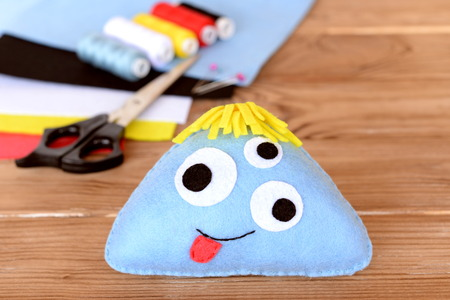 Funny toy monster with three eyes. Blue felt monster, felt sheets, thread set, scissors on lilac wooden background. DIY Halloween idea for kids 版權商用圖片
