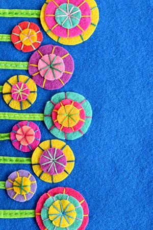 Mehrfarbige Blumen auf einem blauen Filzblatt. DIY Design und Dekor. Auf helle Blumen nähen. Urlaub Hintergrund. Grußkarte zum Geburtstag, Muttertag, Ostern. Bunte Sommerpostkarte Standard-Bild
