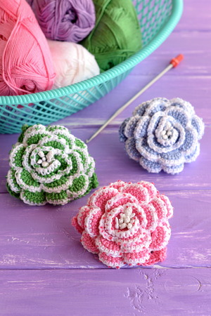 Pink, green and blue crochet flowers decorated with beads. Cotton yarn skeins in basket, hook and bright knitted roses on lilac wooden background. Beautiful beaded crochet project Stock Photo