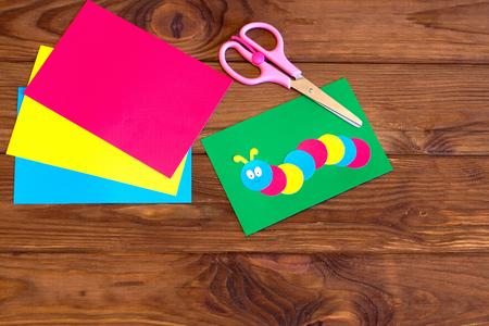 Children paper applique - colored caterpillar on green leaf, paper sheet, scissors. Brown wooden background