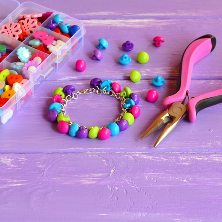 Bright colored bracelet made of plastic buttons. Handmade cute kids jewelry. Children's diy. Organizer with wooden and acrylic buttons, pliers