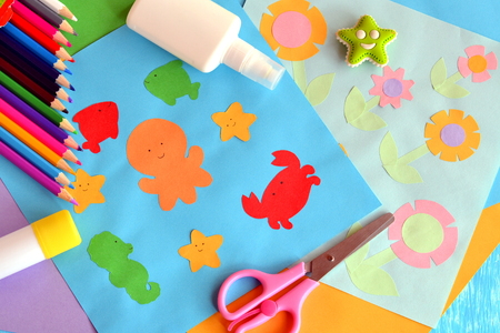 children crab: Paper octopus, fish, starfish, crab, flowers. Project idea using a colored paper. Applique work for children. Crafts from colored paper. Glue, scissors, pencils, eraser. Funny background Stock Photo