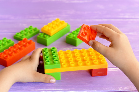 Little child holds a designer blocks in his hands and does bed toy. Colored plastic constructor on lilac background. Toy building blocks into game. Child masters fine motor skills Stock Photo