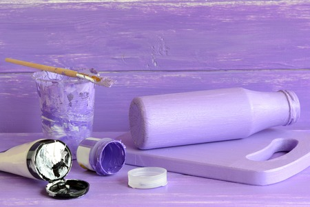 wood craft: Handmade decor glass milk bottle. Glass jar crafts. How to make decoration at home with waste material. Home accessories. Lilac and white acrylic paint, brush Stock Photo