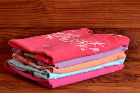 Stack of colorful clothes for baby girls on a wooden background. Collection of girls raglan cotton. Red, lilac, orange, pink, blue children clothes stacked in a pile. Close-up