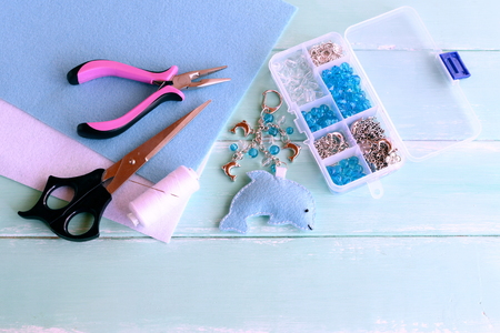 Felt dolphin keychain design. Dolphin bag pendant out of felt and beads. Summer kids sewing project. Scissors, pliers, felt sheets, thread, needle, plastic box of beads and metal pendants Stock Photo