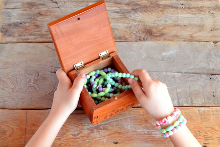opens: Little girl opens a box of bracelets. Old wooden background Stock Photo
