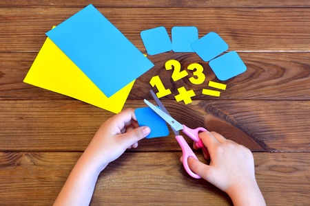 Child holds the scissors and cuts paper card. Paper sheets and numbers on a brown wooden background. Education concept Stok Fotoğraf