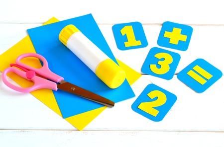 Handmade paper cards with numbers, scissors, paper sheets, glue on a white background