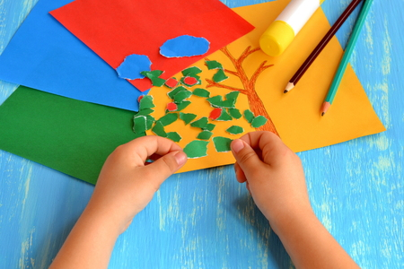 Child tearing colored paper into pieces. Home activity to improve fine motor skill development. Baby play. How to work with paper and glue. Color paper sheets, glue stick, pencils. Blue background