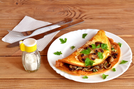 Delicious omelet with slices of fried mushrooms, grated cheese, fresh parsley on the plate. Fork, knife, napkin, salt shaker. Wooden table. Healthy omelet for breakfast. Fried eggs omelett