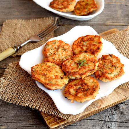 Chuletas fritas de pescado picado en el plato. Bifurcación, tabla de cortar, arpillera en fondo de madera. Receta de salmón delicioso y saludable Foto de archivo