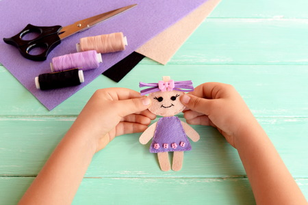Child holds a felt doll in his hands and shows it. Scissors, thread, felt sheets on a table. Cute stuffed toy is made manually. Easy sewing project for kids Stock Photo