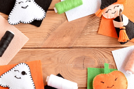 Halloween felt craft embellishments. Hand made witch with broom, pumpkin head, two ghosts. Mixed Halloween ornaments, colored felt sheets on wooden table with copy space for text. Fall background Stock Photo