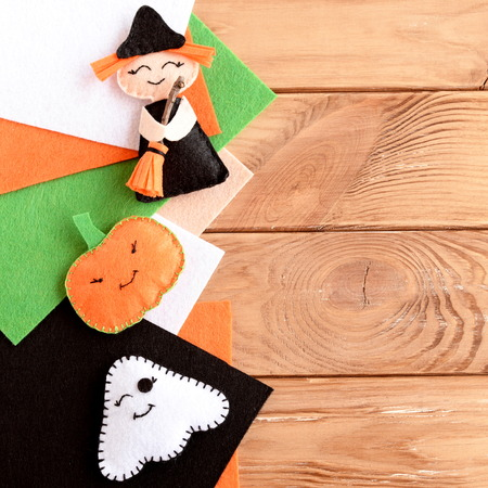 embellishments: Pretty Halloween embellishments toys and felt sheets on wooden background with blank space for text. Little witch, pumpkin head and ghost made out of felt. Kids crafts. Halloween background