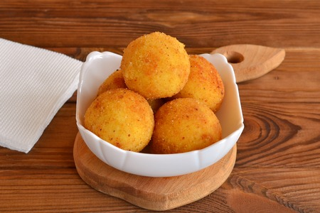 Arancini balls on a plate. Fried rice cutlets recipe. Brown wooden background