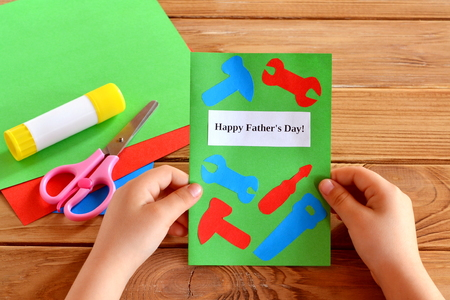 Child holds greeting card in his hands happy fathers day paper child holds greeting card in his hands happy fathers day paper craft idea project m4hsunfo