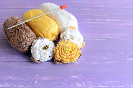 Yellow and white beaded crochet roses, skeins of cotton yarn, crochet hook on wooden background. Easy colored flowers patterns. Crafts for beginners. Handicraft concept