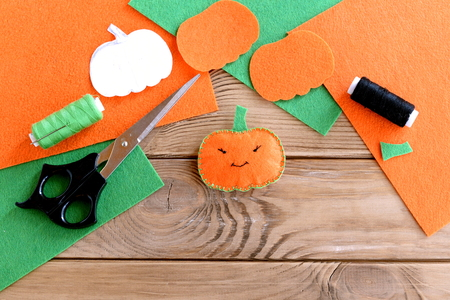 Halloween mini pumpkin decor. Orange felt pumpkin toy, scissors, flat pieces of felt, green and black thread, needle, paper template on wood background. Halloween sewing crafts