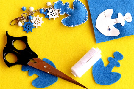 Felt anchor keyring, scissors, thread, pins, paper pattern, blue felt piece on yellow background with empty place for text. Handicrafts project for kids. Keychain crafts for car or beach bag. Top view