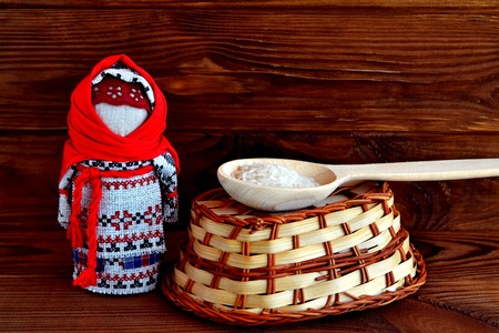 belarusian ethnicity: Folk Russian doll, a spoon of rice, a basket, a tradition. Old brown wooden background