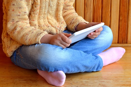 sits: Child sits holding a tablet in hands. Wooden background