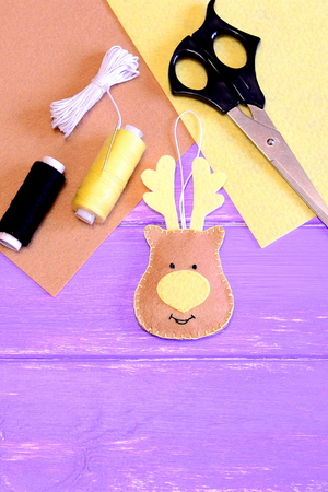 Cute Christmas deer made of felt. Yellow and brown felt pieces, thread, needle, scissors on lilac wooden background with copy space for text. Creating of Christmas decorations concept. Top view Stock Photo